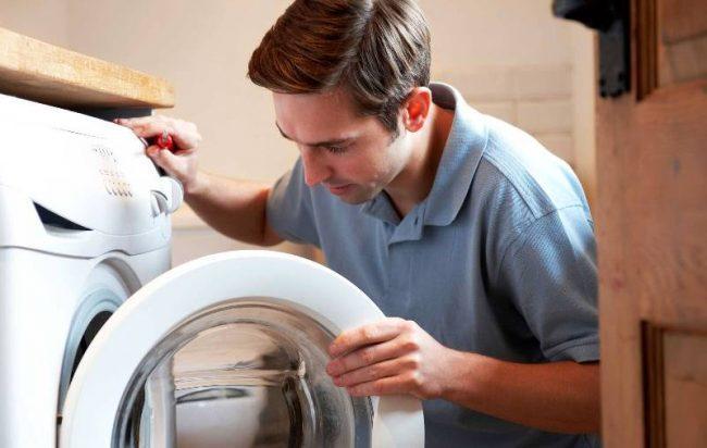 Мужчина открывает стиральную машинку